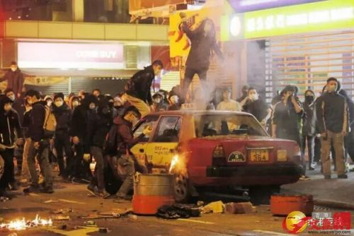 """""""旺角暴乱"""",有暴徒用砖头砸毁停泊在路边的士及大肆破坏。(图片来源:文汇网)"""
